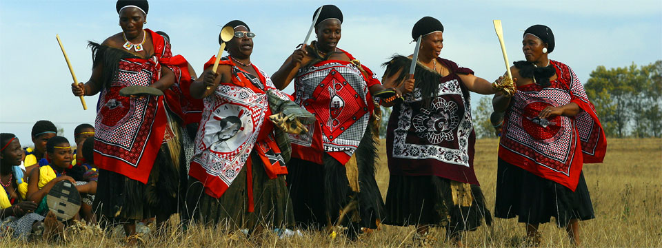 Elderly woman in traditional dress perform a cultural dance in Swaziland